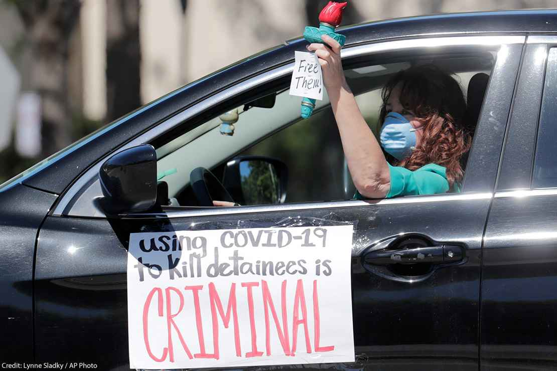 A woman drives in a caravan protesting conditions detainees face in ICE detention centers.