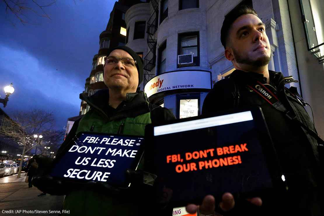 """Demonstrators display iPads with the messages """"FBI: Please don't make us less secure"""" and """"FBI, don't break our phones!"""""""