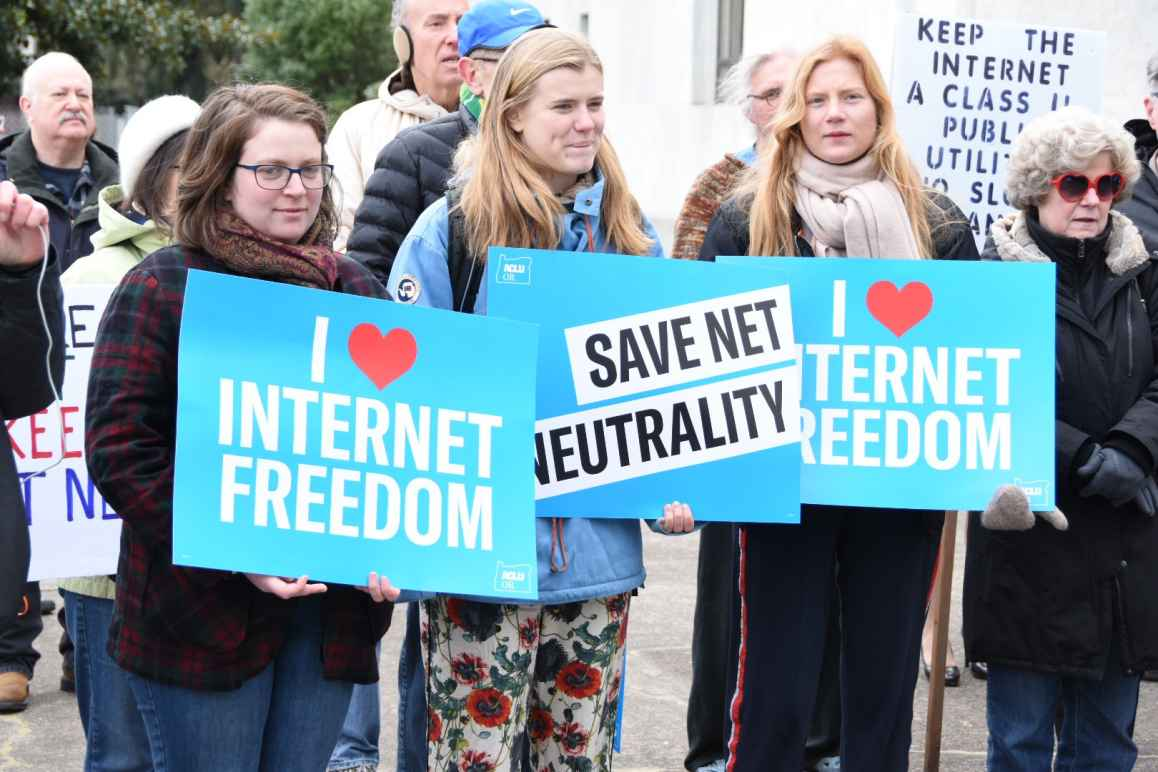 people holding signs that say i (heart) internet freedom and Save Net Neutrality on the capitol steps in Salem