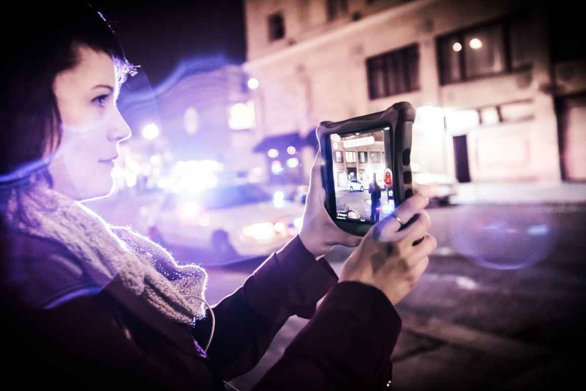 Carrie Medina holds a tablet to film the police on the street. Police lights blur into the foreground.