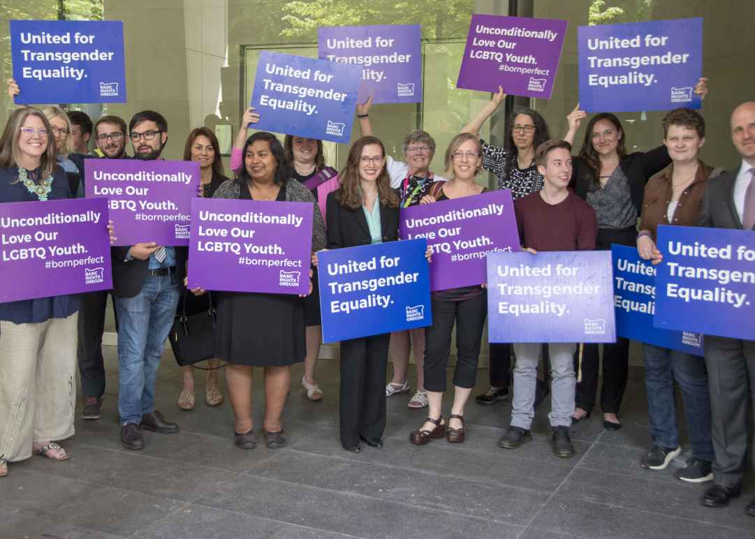 advocates outside court holding signs for transgender equality