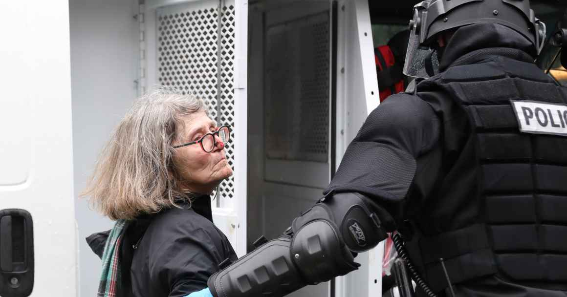 Peggy Zebroski with bloodied face being led into police truck by riot officer